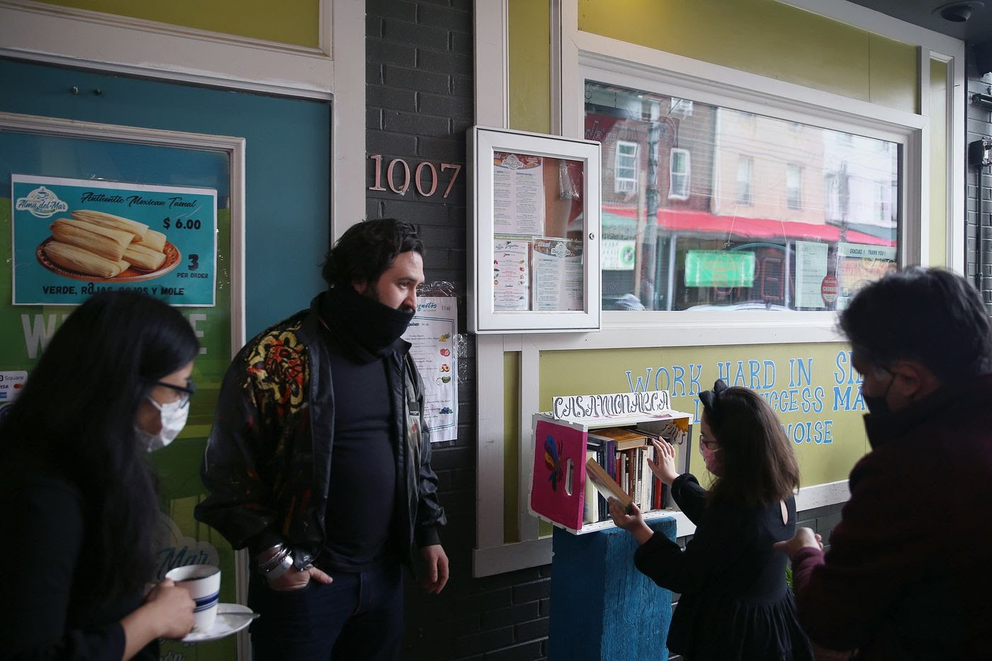 """Organizers Dulce Ramirez (left), Carlos José Pérez Sámano (second from left), and Edgar Ramírez (right) gather as Ellie Guzmán, 8, daughter of organizer Reyna Casarez (not pictured), looks at books in the newly installed """"huacalibrero"""" outside Alma del Mar in South Philadelphia."""